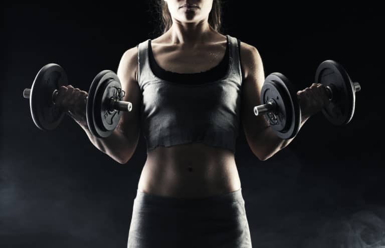 Getting In Shape Young woman lifting the dumbbells