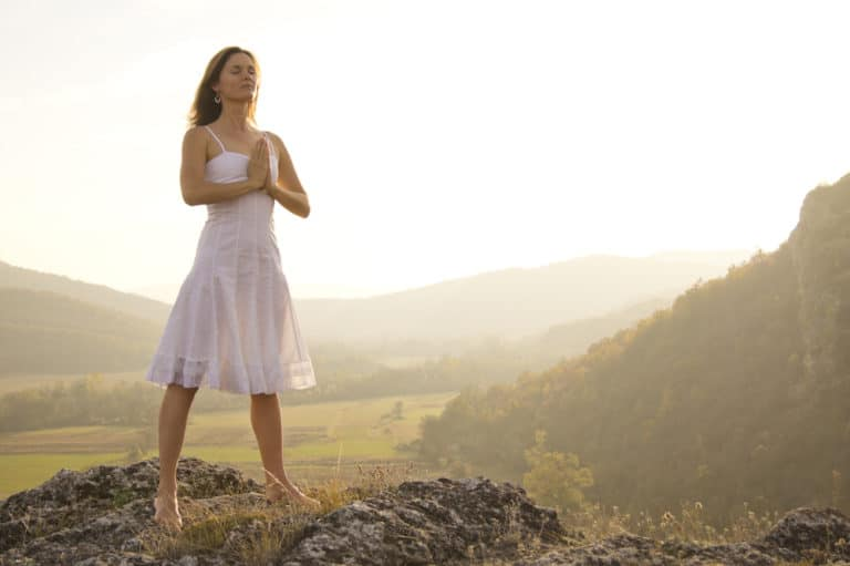 Be Obsessively Grateful Young woman standing in meditation on the top of a hill