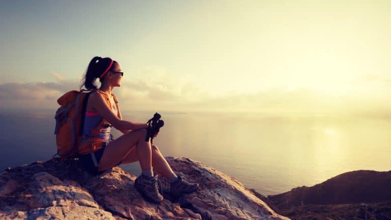 Enjoy the Journey young woman hiker at sunrise seaside mountain peak