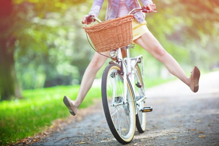 Less Stress and More Joy Woman riding bicycle with her legs in the air