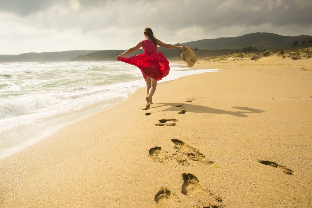 Less Stress and More Joy Beautiful happy woman running freely on the beach